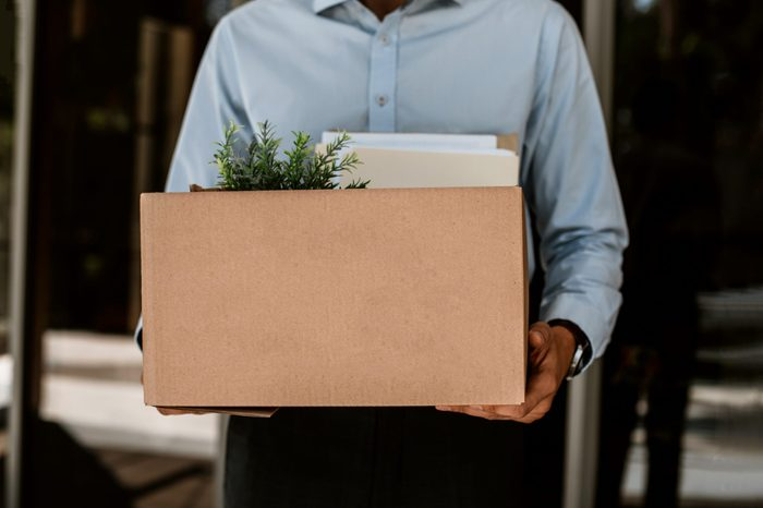 Close up of box with working stuff including pot plant and documents. Fired man is standing outside and holding all his things after leaving company