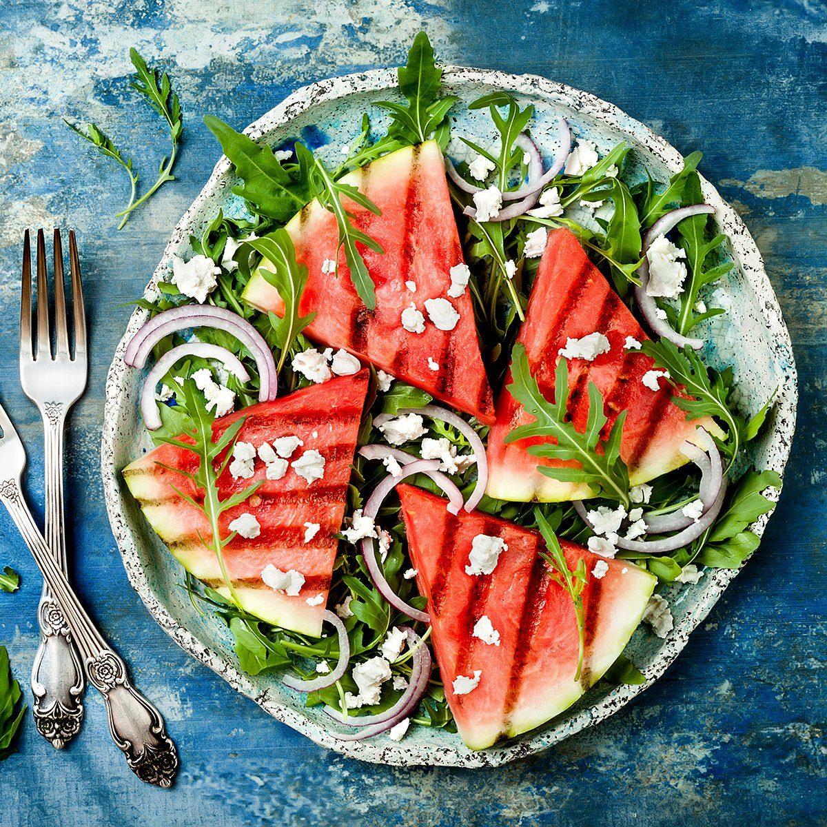 Fresh summer grilled watermelon salad with feta cheese, arugula, onions on blue background