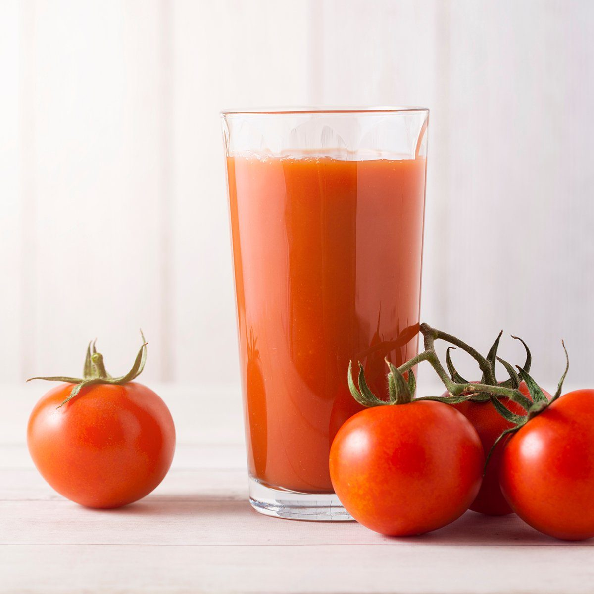 Glass of fresh organic tomato juice with raw tomatoes on light wooden background