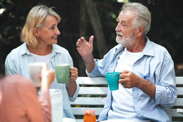 Family lunch outdoor. Couple of white and asian senior man and woman sitting and holding coffee cup other in tropical garden.