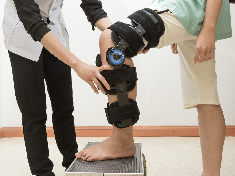 Therapist fitting a knee brace to a patient