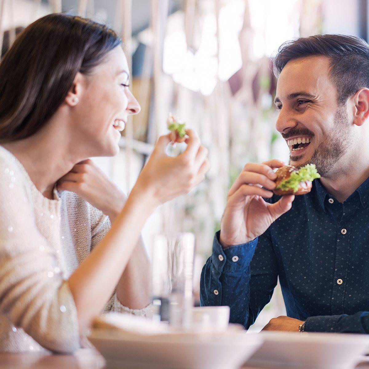 Happy loving couple enjoying breakfast in a cafe.