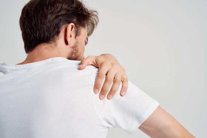 a man in a white shirt touches his shoulder with his hand