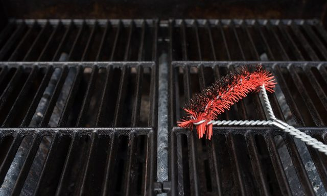 Close up focus of a scrubbing utensil used for cleaning a dirty grill. BBQ Grill Background Theme