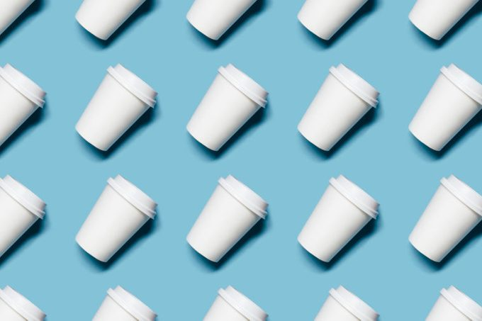 Pattern with lot of paper cups for coffee or tea on blue background.
