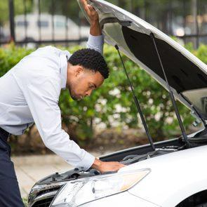 Car won't start - man looking under hood of car