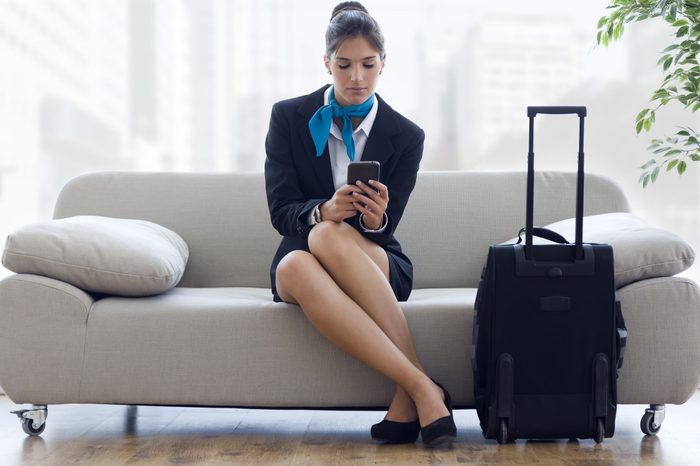 Portrait of beautiful hostess in airport with mobile phone.