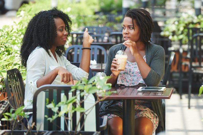 Two pretty Africa-American women drinking cocktails and chatting in cafe