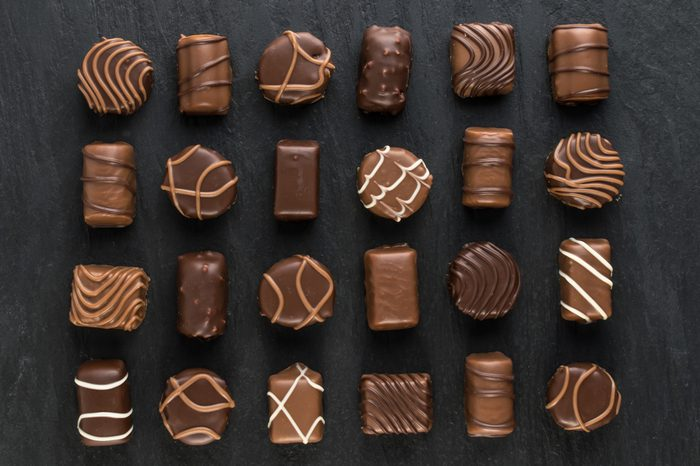Beautiful Creative Chocolate Sweets on Natural Black Stone Background. Mix of Chocolates Top View and Flat Lay