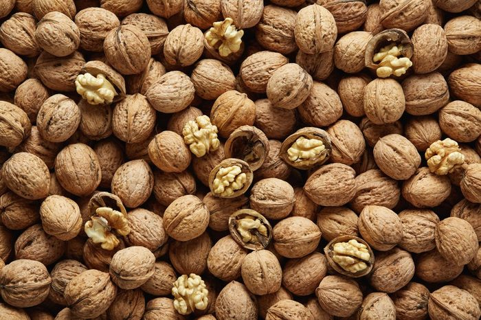 Walnuts with and without shells (filling the picture). Background of fresh walnuts.