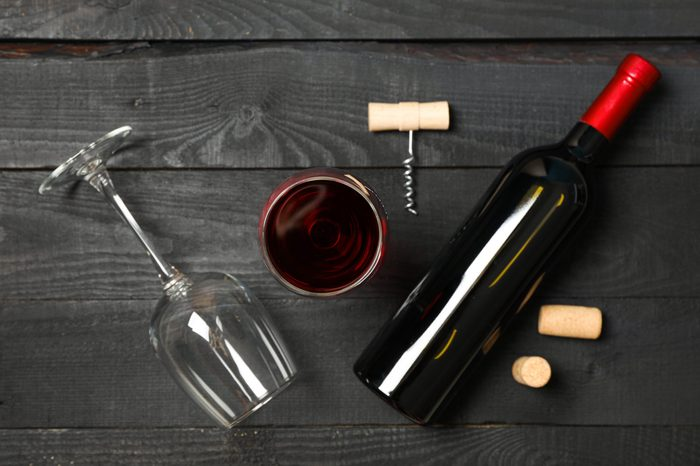 Flat lay composition with bottle of wine, glasses and corkscrew on wooden background, copy space