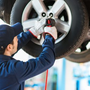 Mechanic changing car tire in auto repair shop