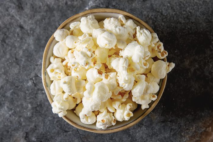 Salted popcorn in a cup. Dark background. Selective focus. Fast food for movies