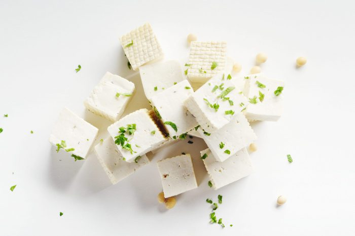 Soy Bean curd tofu with greens on white background Non-dairy alternative substitute for cheese