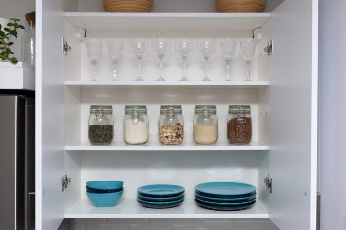 Various seeds in storage jars in pantry, white modern kitchen in background. Smart kitchen organization