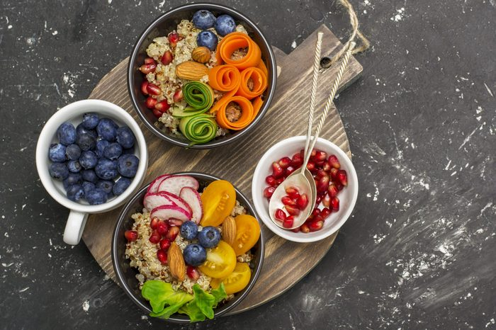 Vegetarian Quinoa bowl. Healthy breakfast or snack with detox quinoa, tomato, cucumber, carrot, pomegranate seeds, juicy blueberries and lettuce in portioned bowls. Top
