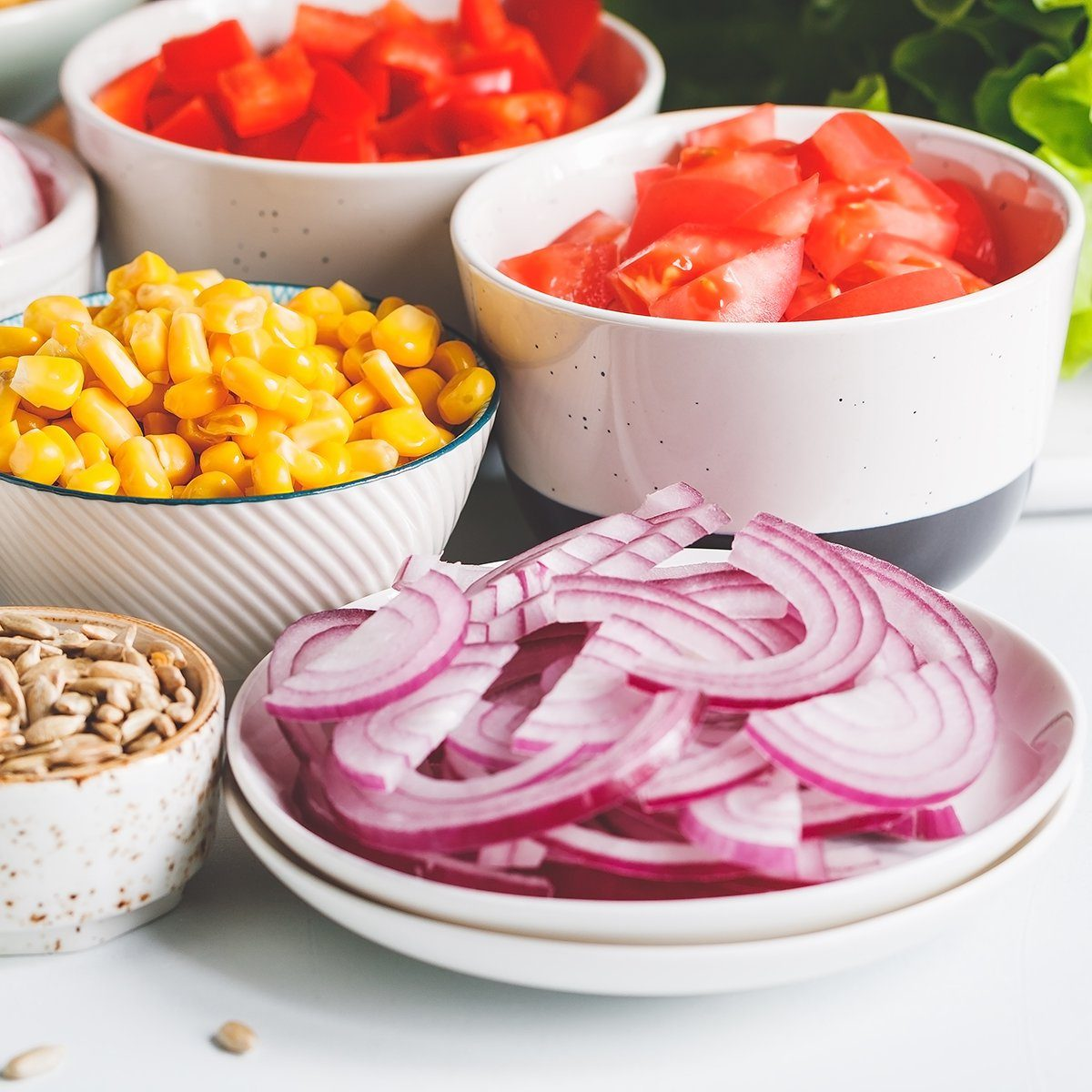 Assortment ingredients for healthy vegetarian salad in different portion bowls on a table.