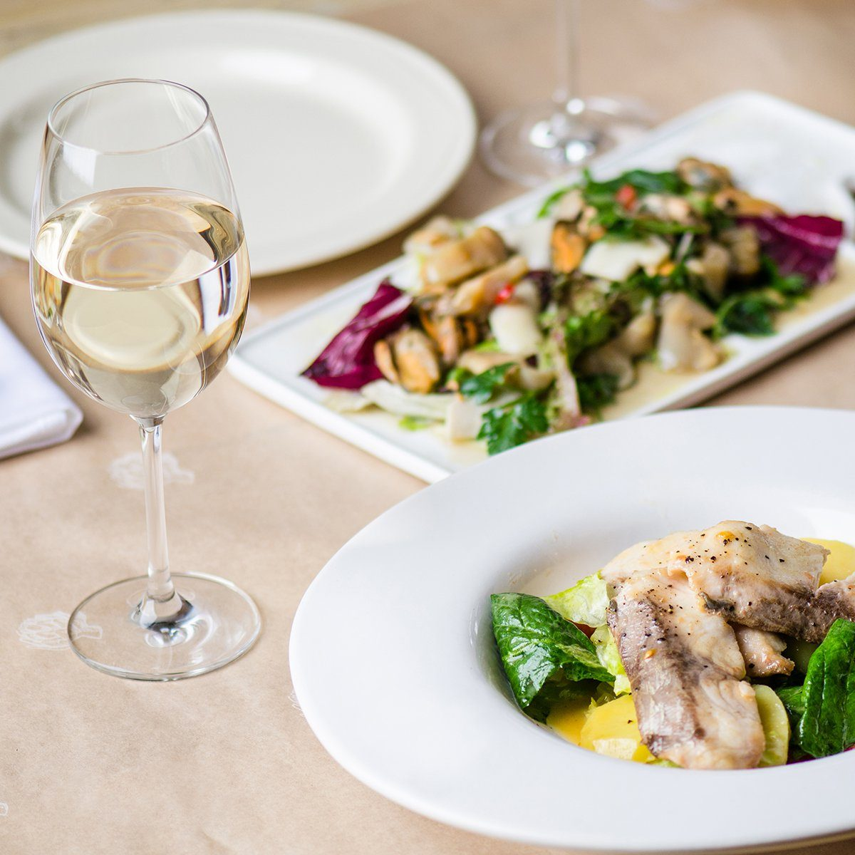 Fish fried with vegetables , seafood salad and white wine - a lovely dinner for two . Living healthy food . Close-up in white plate on the served table.