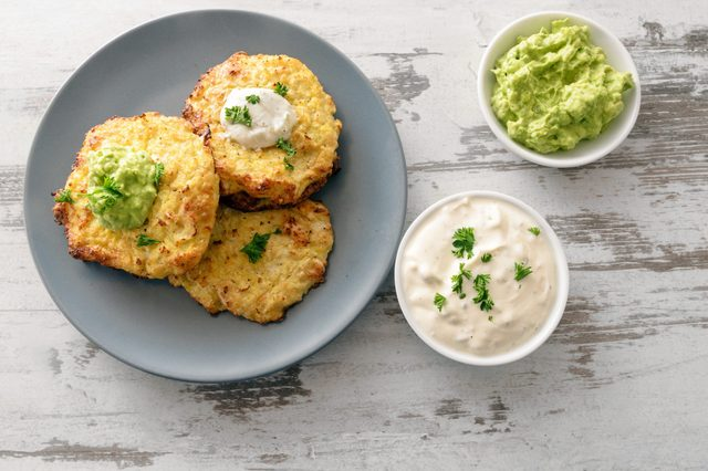 healthy vegetable rosti from cauliflower and parmesan cheese, dips from sour cream and avocado, parsley garnish, blue plate on a bright rustic wooden table with copy space, high angle view from above