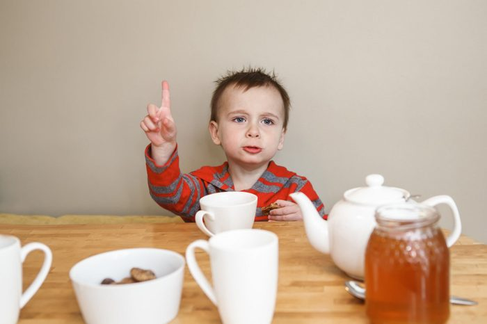 Close-up candid natural portrait of cute little boy toddler in kitchen drinking tea juice, making funny face, showing finger, lifestyle documentary style, grainy film effect