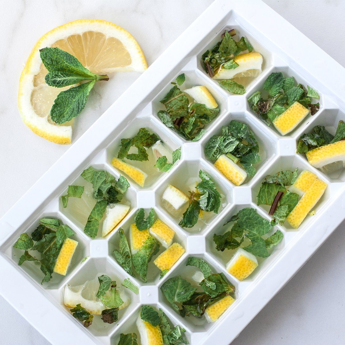 Cooking ice cubes with lemon and mint on marble background.