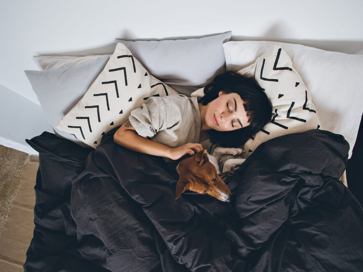 Health studies - woman sleeping in bed with her pet dog