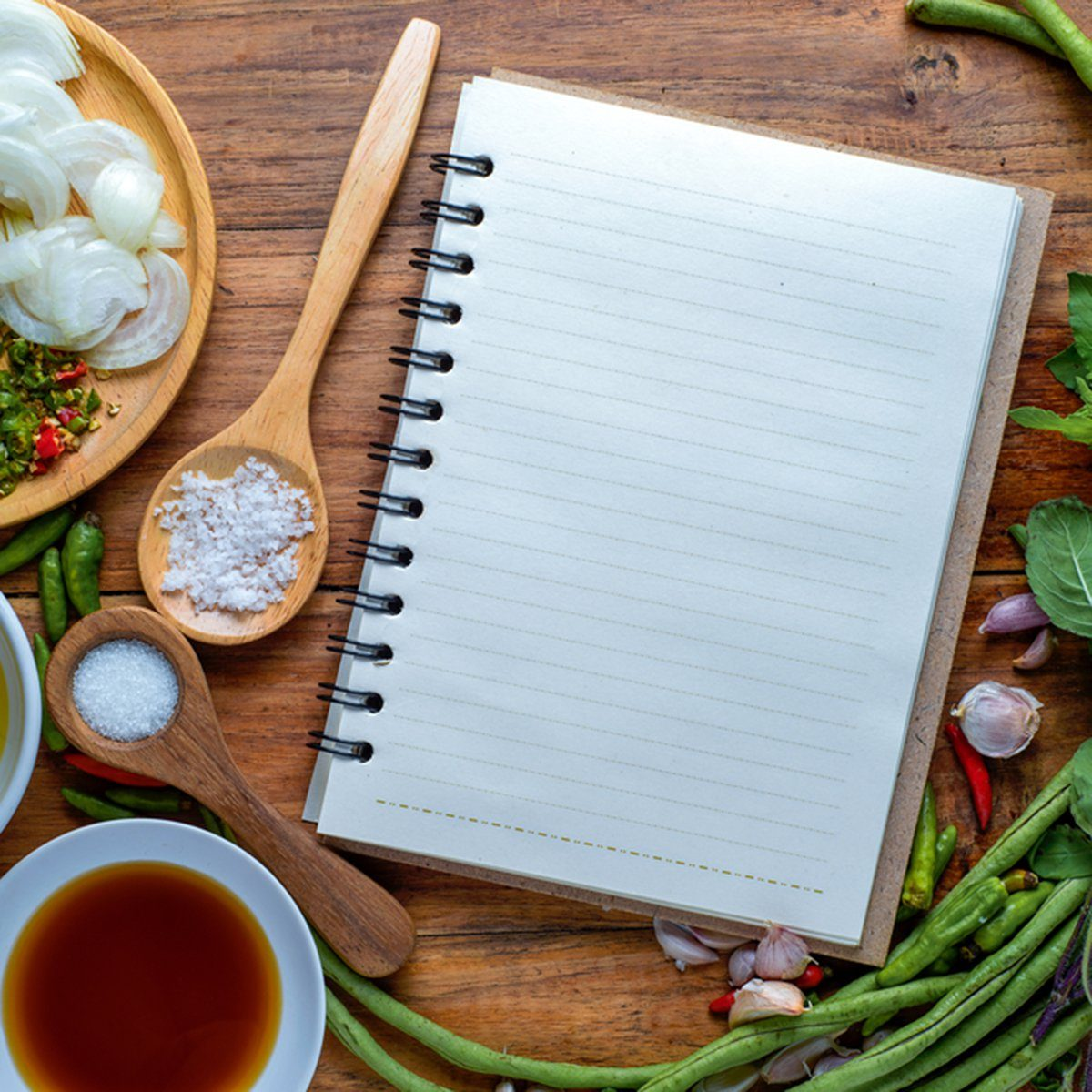 recipe book with fresh herbs south asia and spices on wooden background