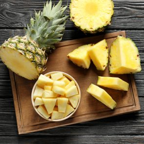 Wooden board with fresh sliced pineapple on table
