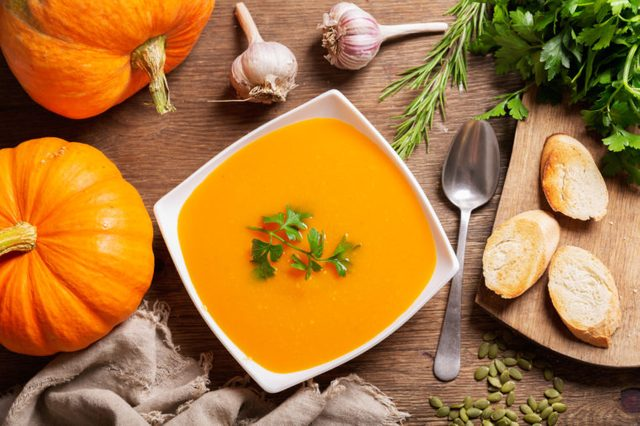 bowl of pumpkin soup with ingredients for cooking, top view