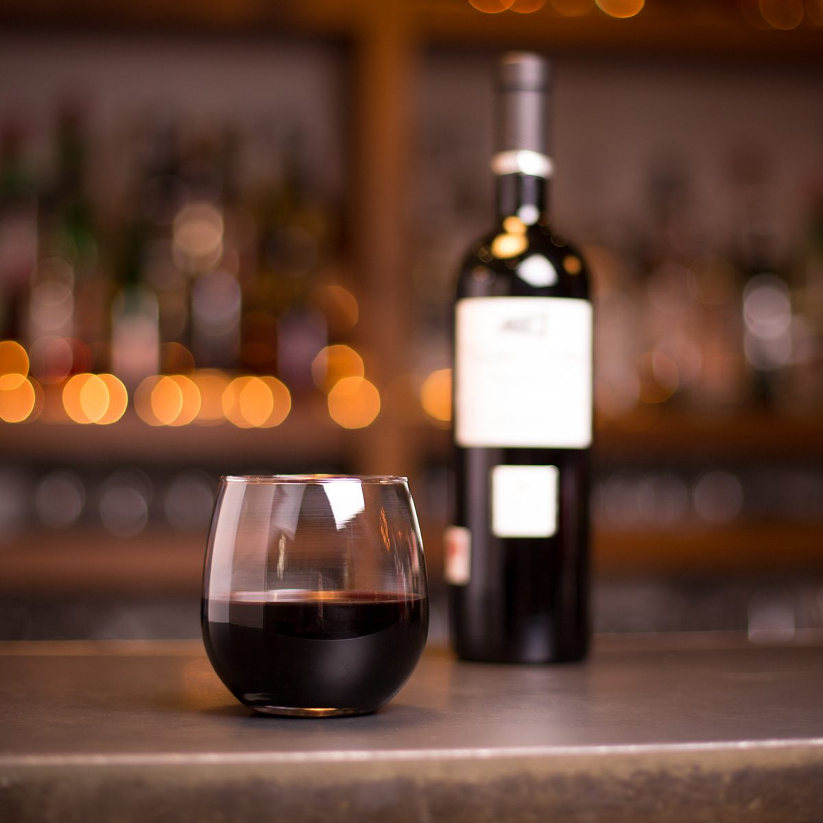 Low angle close up perspective of crystal clear stemless wine glass with traditional round goblet shape filled with rich red wine on metal counter top bar with blurry bottle and restaurant background