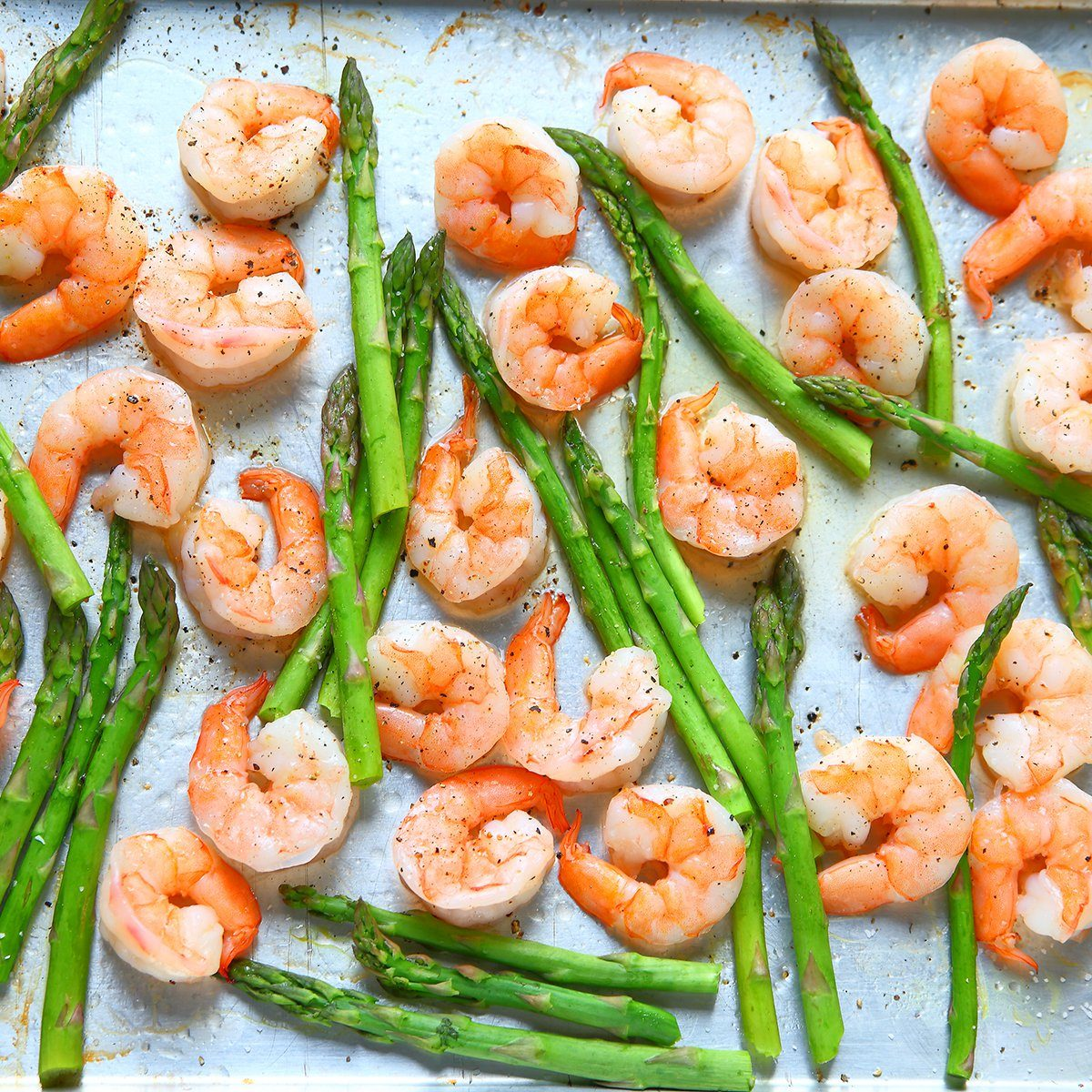 Sheet pan dinner of shrimp and asparagus with olive oil and black pepper