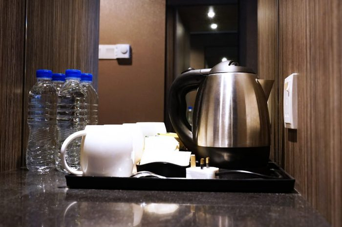 Coffee making set in a hotel room with stainless steel electric kettle, clean cup, teaspoon and bottle of water.