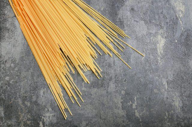 Spaghetti pasta on grey stone background, copy space.