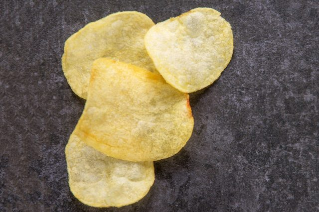 potato chips on the background of black stone, flat lay