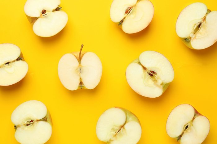Cut fresh apples on color background