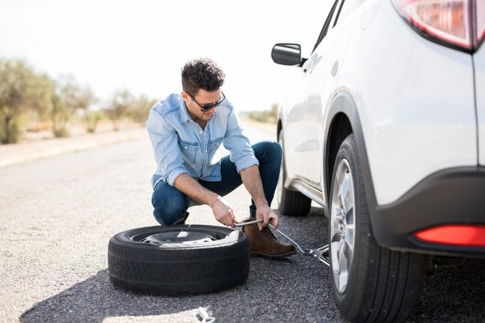 Young man lifting the car on the jack for changing flat tire on the road