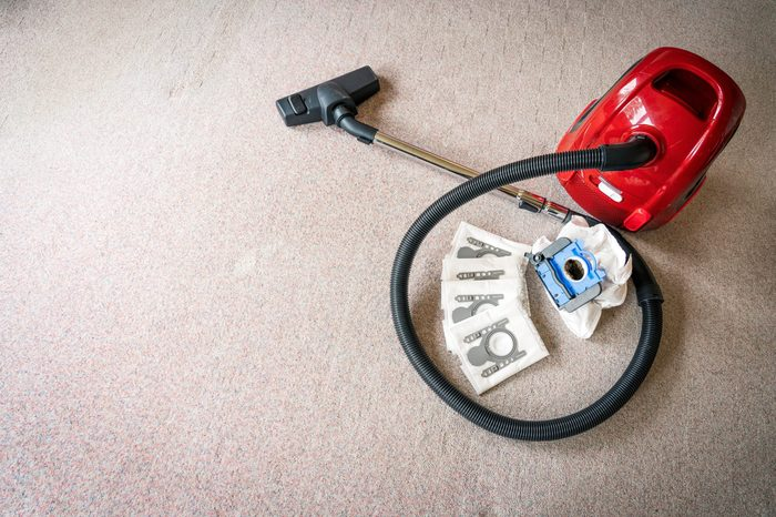 A red vacum cleaner with old and new vacum filter bags laying on a white carpet floor with spacing on the left for text. Cleaning and maintenance concept.