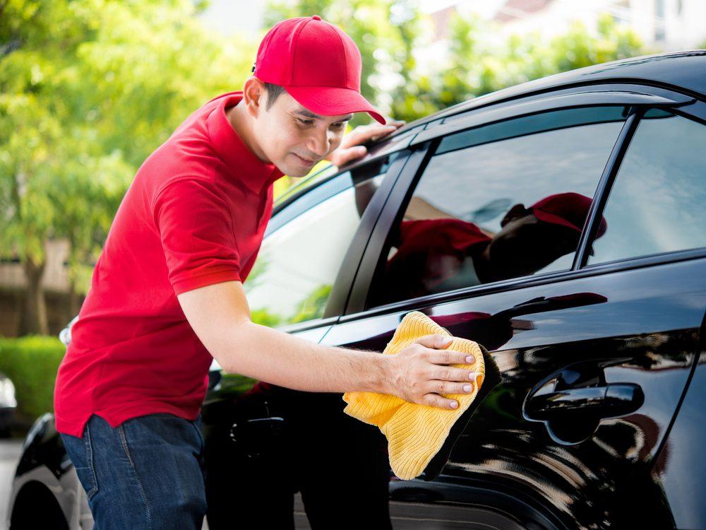 Asian man washing his car
