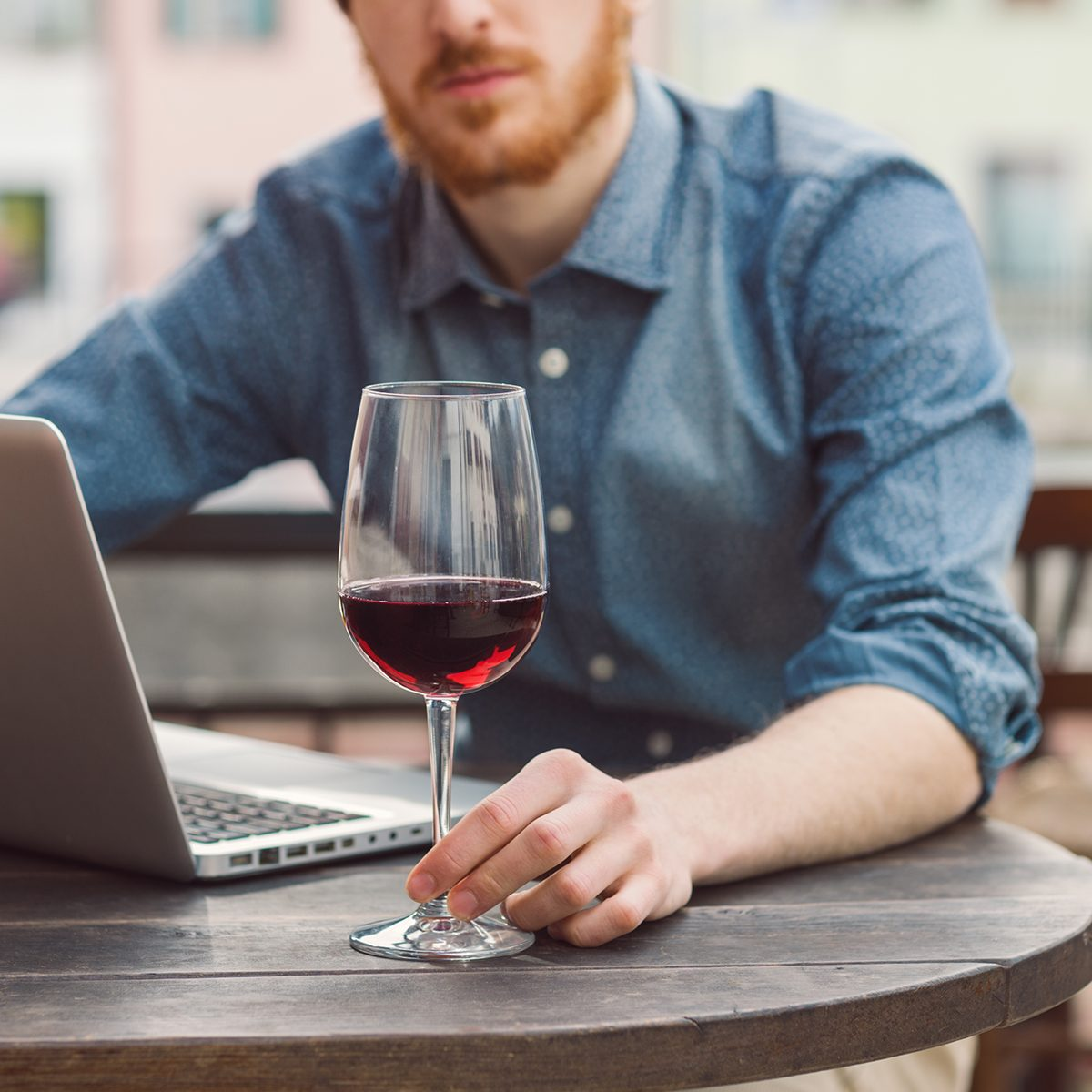 Young hipster man sitting at outdoor bar table with his laptop and having a glass of wine