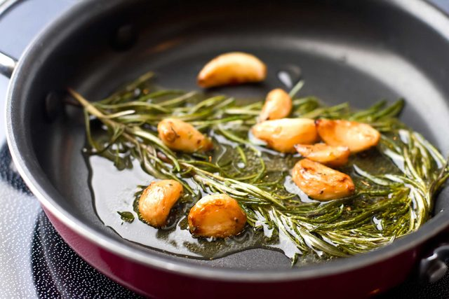 rosemary stems and garlic bulbs in oil on the stove