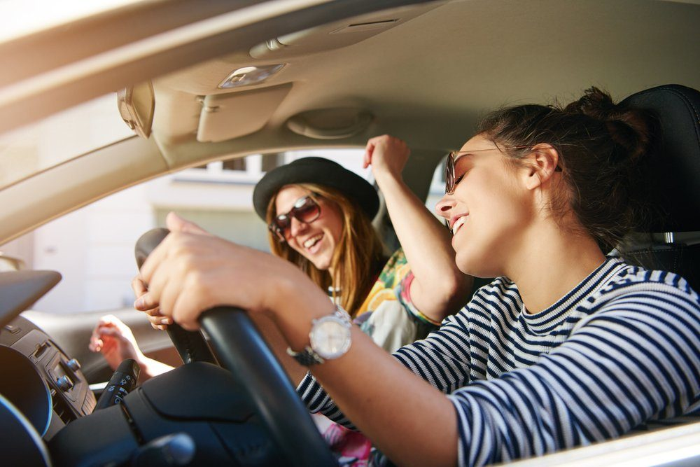 Two trendy attractive young woman singing along to the music as they drive along in the car through town viewed through the open side window