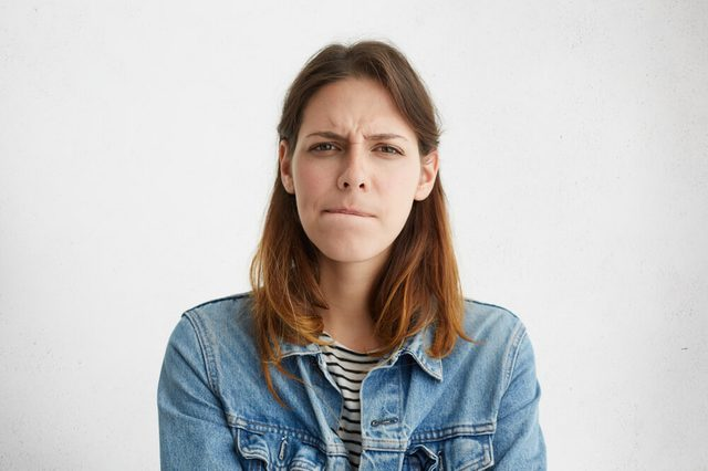 Anxious or worried woman with pursed lips and furrowed brow