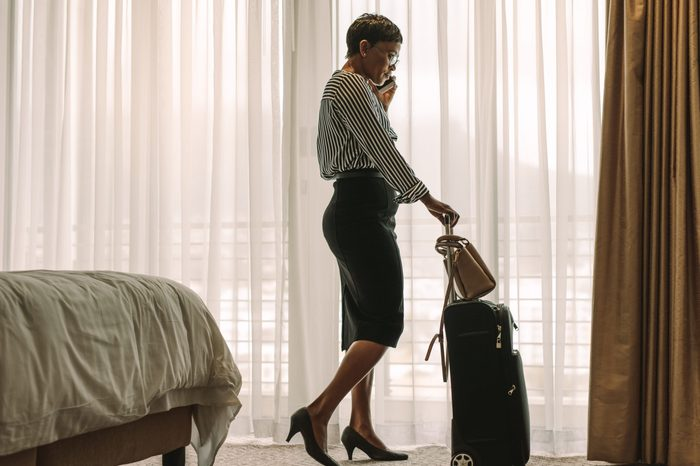 African businesswoman standing by bed in hotel room with her luggage talking over cell phone. Female executive on business tour talking on phone from hotel room.