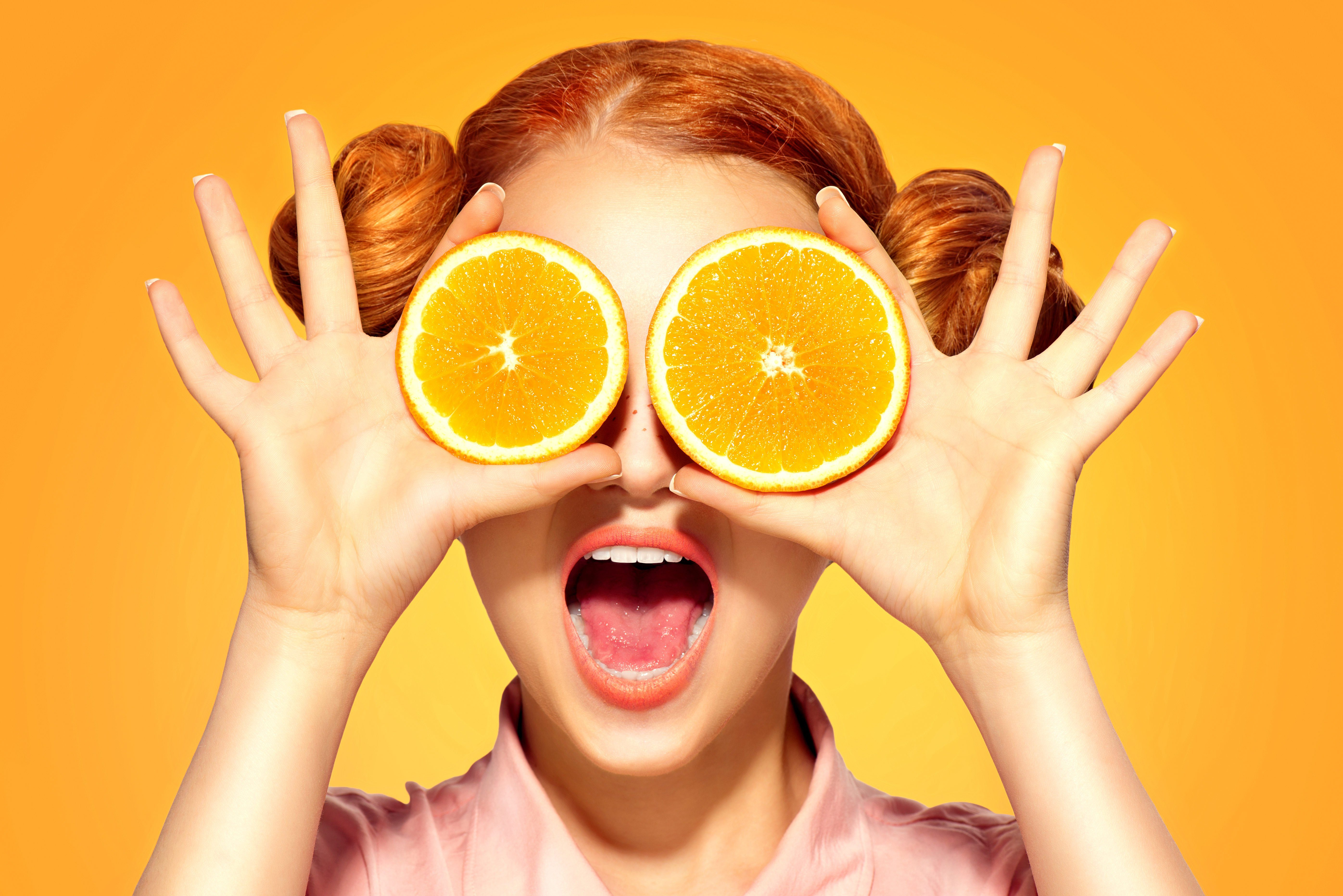 Beauty Model Girl takes Juicy Oranges. Beautiful Joyful teen girl with freckles, funny red hairstyle and yellow makeup. Professional make up. Holding Orange Slices and laughing, emotions