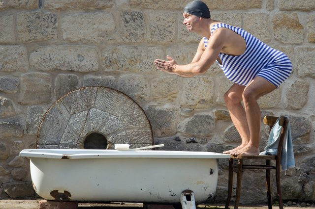 Fat man in retro swimsuit jumps to the outdoor bathtub. Funny swimmer in vintage style and bathing cap starts to swim in the tub. Home vacations. Domestic holiday.
