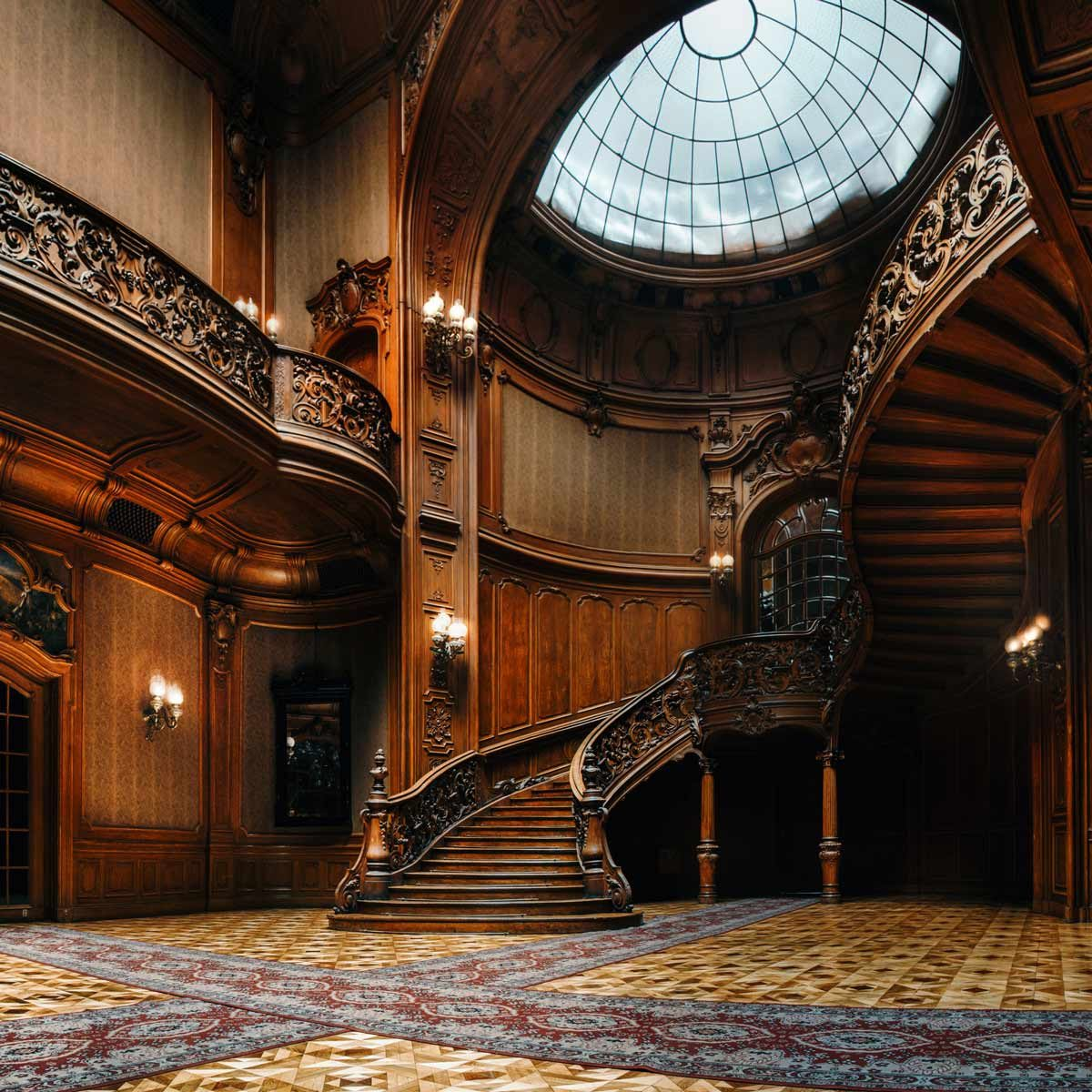 Interior of the magnificent House of Scientists mansion with ornate grand wooden staircase in the great hall.