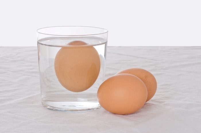 Rotten egg, salmonella risk. Old fashioned test. Bad egg floats in glass of water.