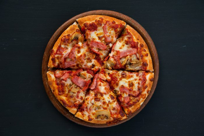 Slices of pizza on rustic wooden tray and dark background