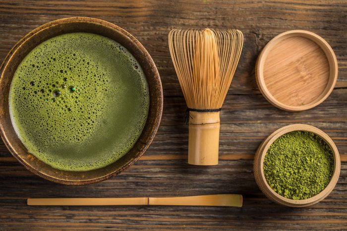 Top view of green tea matcha in a bowl on wooden surface