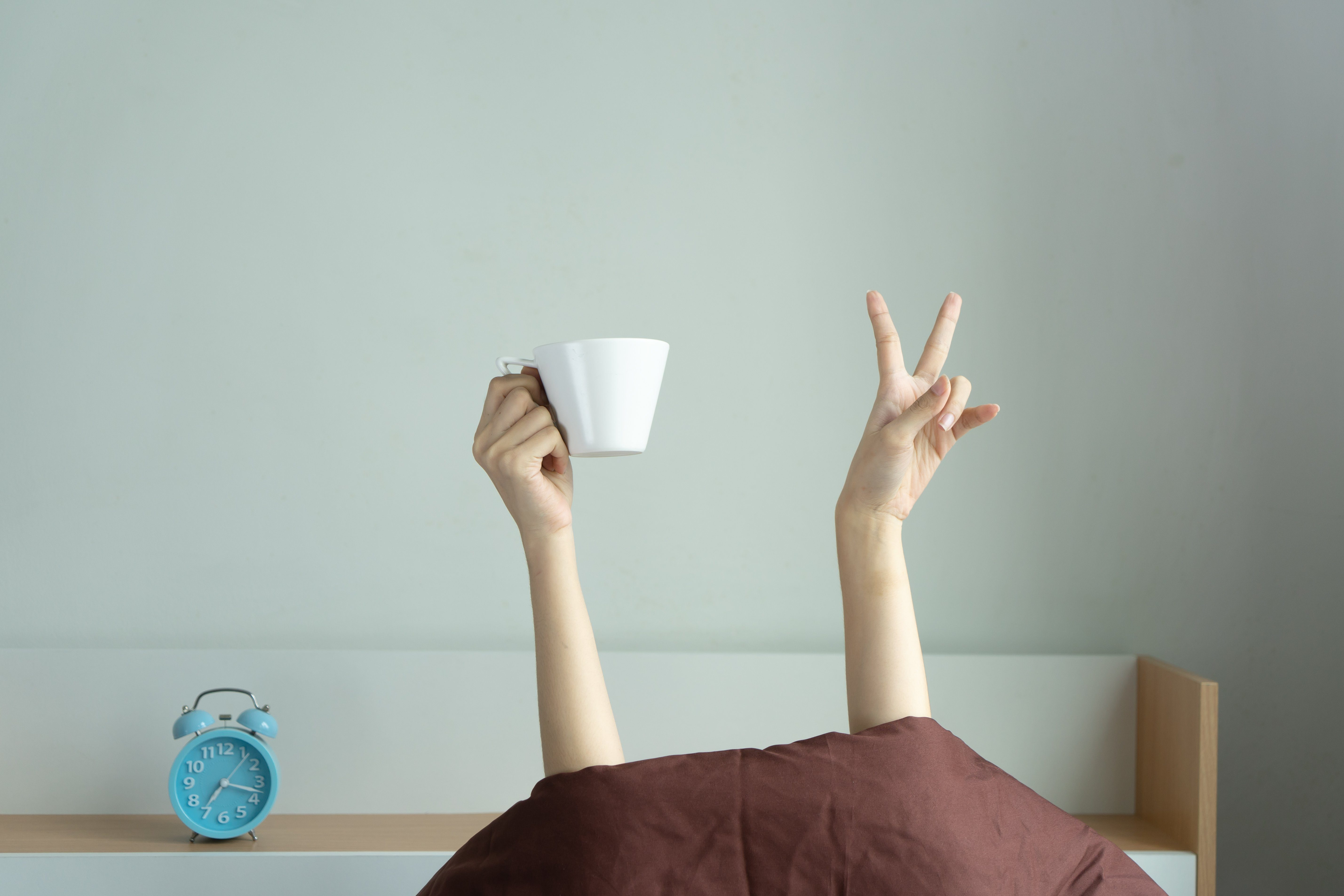 Woman showing funny v sign holding blue tea cup relaxing in bed room, Young woman with two hands drinking coffee in blue cup after awaking. wake up with fun in morning on weekend, love coffee concept.